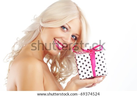Portrait of cute young woman holding wrapped gift - stock photo