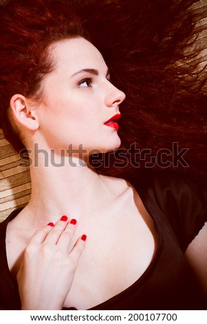 portrait of cute young woman redhead girl with red lips nails lying on sofa & looking at copy space background closeup picture - stock photo