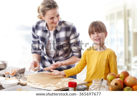 Portrait of cutie girl baking together with her mom at home.