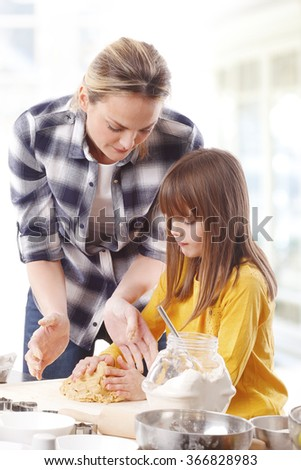 Portrait of cutie little girl baking together with her mom at home.