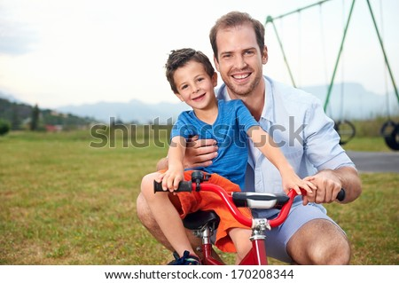 portrait of dad teaching son how to ride his new bicycle in the park, happy smiling family - stock photo