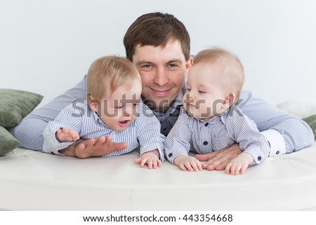 Portrait of dad with twin boys in a children's room lie on the bed on her stomach. - stock photo