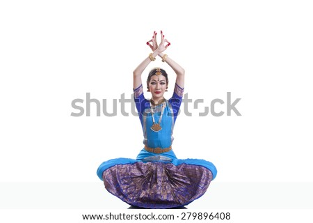 Portrait of dancer with arms raised performing Bharatanatyam against white background - stock photo