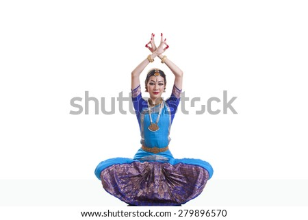 Portrait of dancer with arms raised performing Bharatanatyam isolated over white background - stock photo