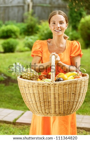 Portrait of dark-haired smiling beautiful young woman in orange blouse with baskets of fruit and vegetables, against green of summer park.