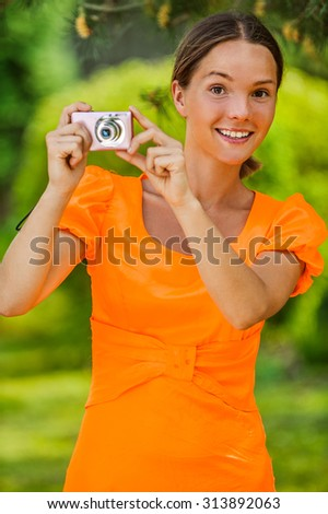 Portrait of dark-haired smiling beautiful young woman in orange blouse with camera, against green of summer park.