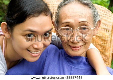 Portrait of daughter embrace her elderly mother lovingly - stock photo