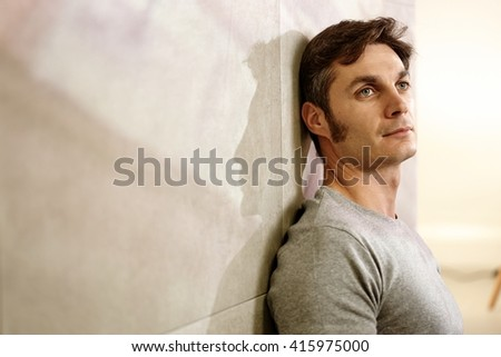 Portrait of daydreaming man leaning against wall, casting a shadow. - stock photo