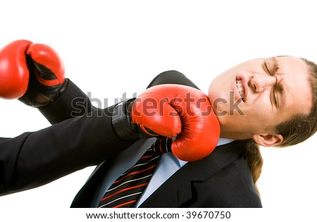 Portrait of defeated businessman in boxing gloves being hit by opponent - stock photo