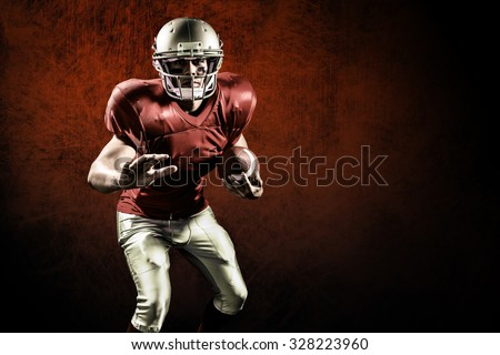 Portrait of defensive sportsman holding American football against dark background