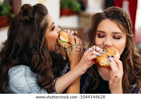 Portrait of delighted teen girls with hairstyles enjoying delicious burgers in cafe.