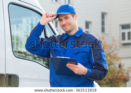 Portrait of delivery man in uniform holding clipboard by truck
