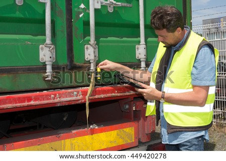 Portrait of delivery man smiling using digital tablet by the truck