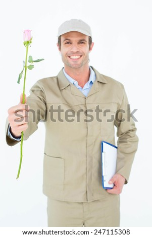 Portrait of delivery man with clipboard offering rose against white background - stock photo