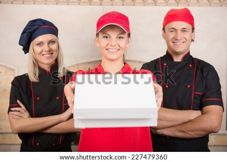 Portrait of delivery woman and two cooks. - stock photo