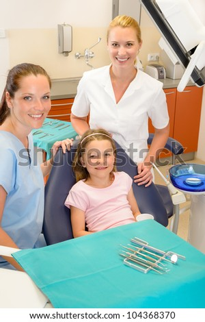 Portrait of dental team with young girl in stomatology clinic - stock photo
