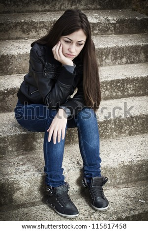 Portrait of depressed teenage girl sitting on staircase. - stock photo