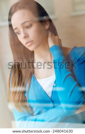 Portrait of depressed young woman sitting at home. - stock photo