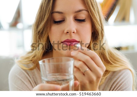 Portrait of depressed young woman taking pills at home.
