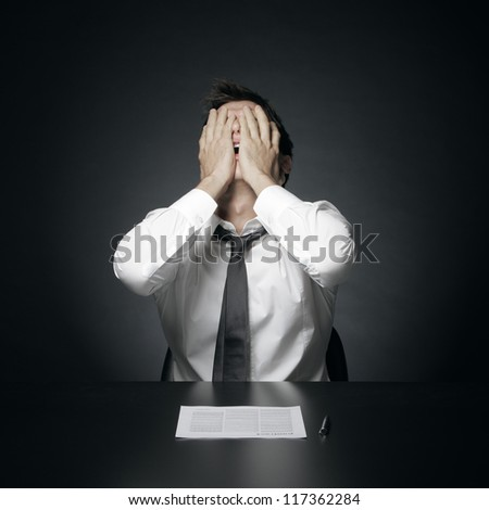 portrait of desperate office manager  covering his face with both hands - stock photo