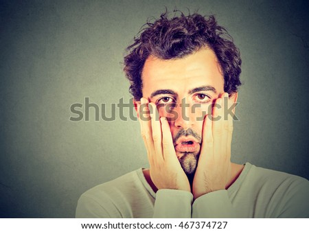 portrait of desperate unhappy man isolated on gray wall background