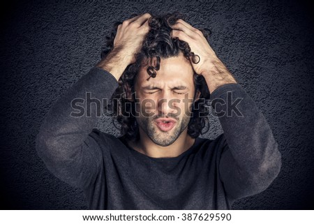 Portrait of desperate young attractive man with curly hair - stock photo