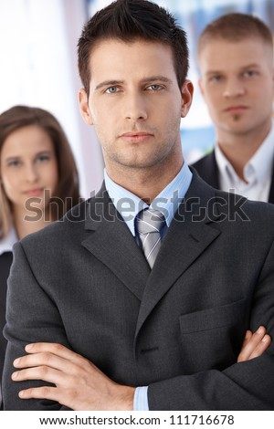 Portrait of determined businessman standing with arms folded, coworkers in background, - stock photo