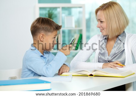 Portrait of diligent boy and his tutor interacting with each other - stock photo