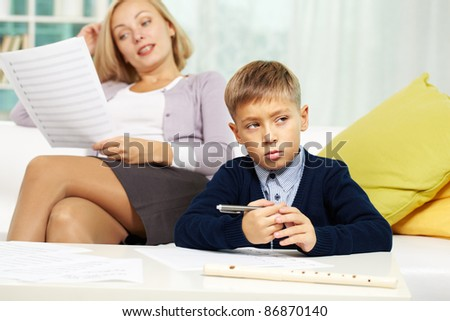Portrait of diligent pupil with musical notes on paper near by and his tutor on background