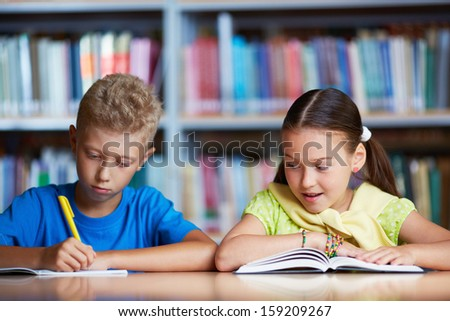 Portrait of diligent schoolchildren reading together in library