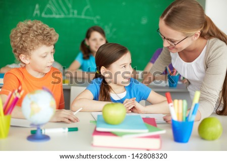Portrait of diligent schoolkids and teacher interacting at lesson
