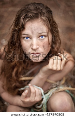 Portrait of dirty grungy young woman wrapped in pieces of rope