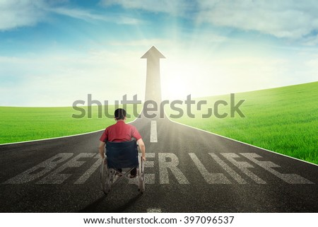 Portrait of disabled man walking on the road with wheelchair toward better life