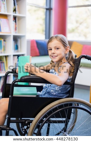 Portrait of disabled school girl on wheelchair holding a books in library at school - stock photo