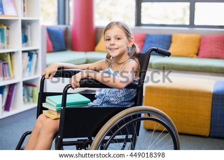 Portrait of disabled school girl with books in library - stock photo