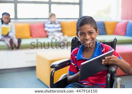 Portrait of disabled schoolboy on wheelchair using digital tablet in library at school - stock photo