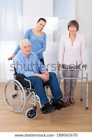 Portrait of disabled senior couple with female caregiver at nursing home