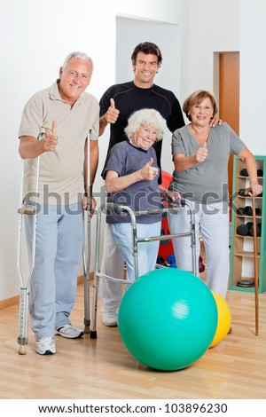 Portrait of disabled senior people with trainer showing thumbs up sign - stock photo