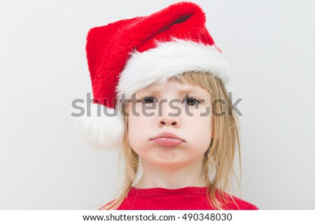 portrait of disappointed little blond girl wearing santa claus hat with big sad dark eyes, no jolly, no present