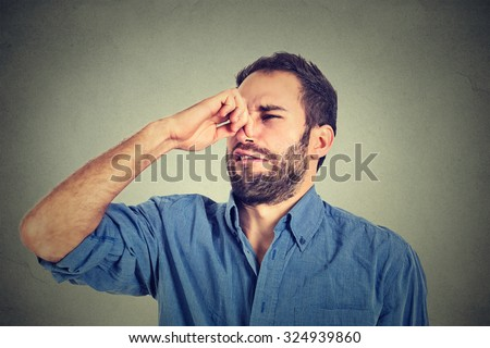 portrait of disgusted man pinches nose with fingers hands looks with disgust something stinks bad smell situation isolated on gray wall background. Human face expression body language reaction - stock photo