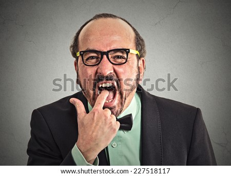 portrait of disgusted man with finger in mouth very displeased with situation service ready to vomit throw up isolated on grey wall background. Human face expression, emotion, feeling, body language