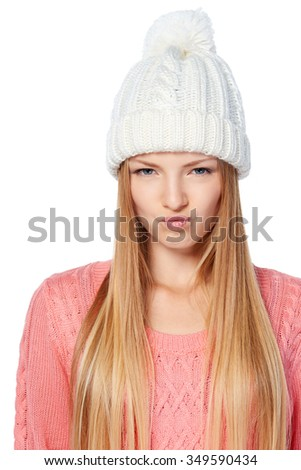 Portrait of displeased woman wearing winter clothing pulling funny face