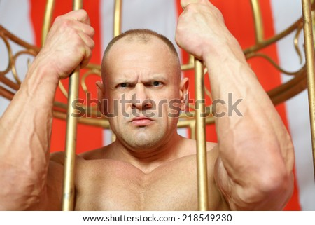 Portrait of dissatisfied athlete behind bars - stock photo