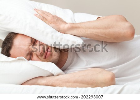 Portrait of dissatisfied Young Caucasian man in bed