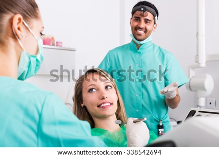Portrait of doctor and positive russian patient at dental clinic - stock photo
