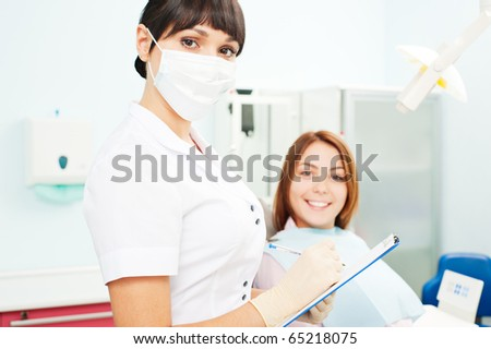 portrait of doctor and smiley patient at dentist's office
