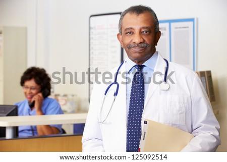 Portrait Of Doctor At Nurses Station - stock photo