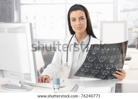 Portrait of doctor sitting in office holding xray image, working on computer, smiling at camera.? - stock photo