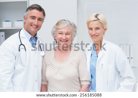 Portrait of doctors and senior patient smiling in clinic - stock photo