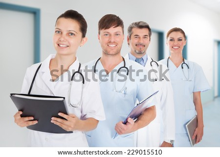 Portrait of doctors with documents and digital tablet standing in row at hospital - stock photo